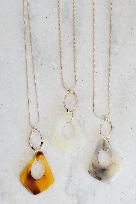 Clear, Taupe, and Ivory Acrylic Pendant Necklaces Flat Lay