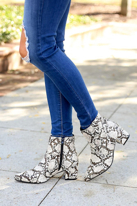 Brown - Side view of snakeskin booties paired with dark wash denim