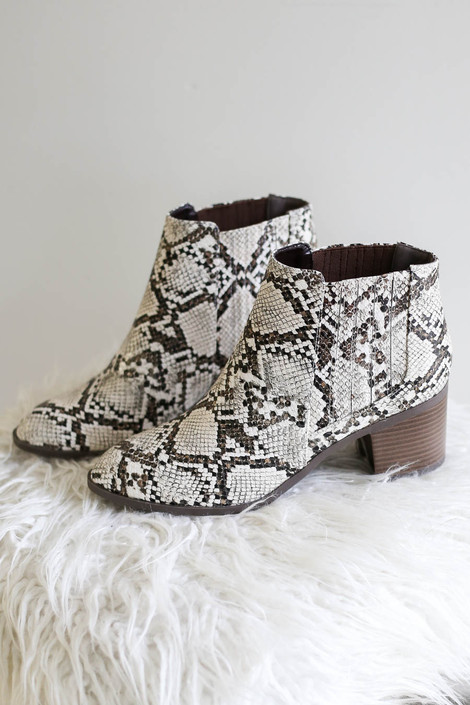 Dress Up Model wearing Ivory Snakeskin Wooden Heel Ankle Booties Product Photo