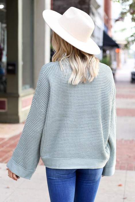 Model wearing the Loose Knit Wide Sleeve Sweater  in Sage from Dress Up Boutique - Back View