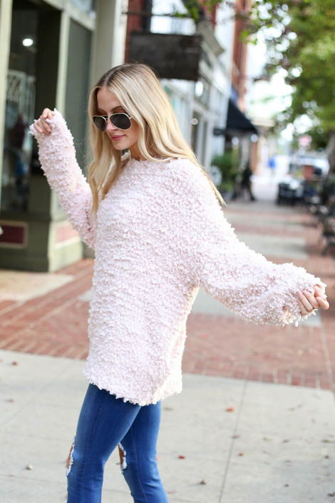 Model wearing the Blush Fuzzy Popcorn Knit Oversized Sweater from Dress Up Boutique - Side View