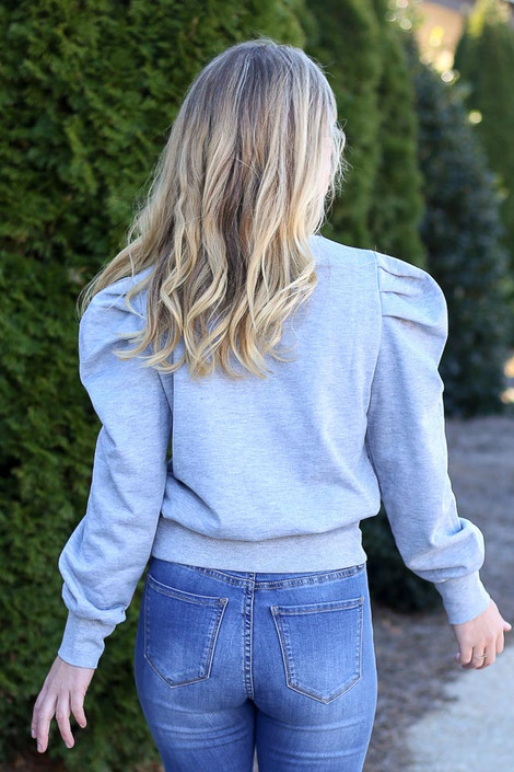 Model wearing the Grey Puff Sleeve Pullover with high rise jeans Back View