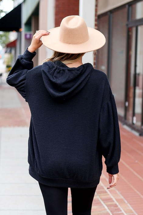 Model wearing the Waffle Knit Balloon Sleeve Hoodie from Dress Up Boutique in Black - Back View