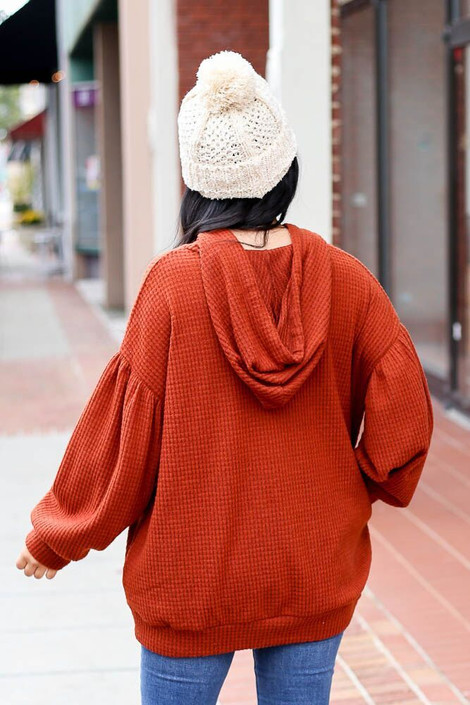 Model wearing the Waffle Knit Balloon Sleeve Hoodie from Dress Up Boutique in Rust - Back View