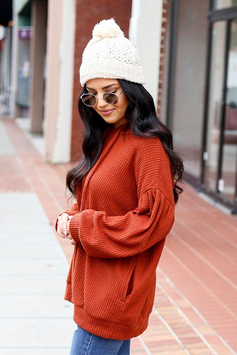 Model wearing the Waffle Knit Balloon Sleeve Hoodie from Dress Up Boutique in Rust - Side View