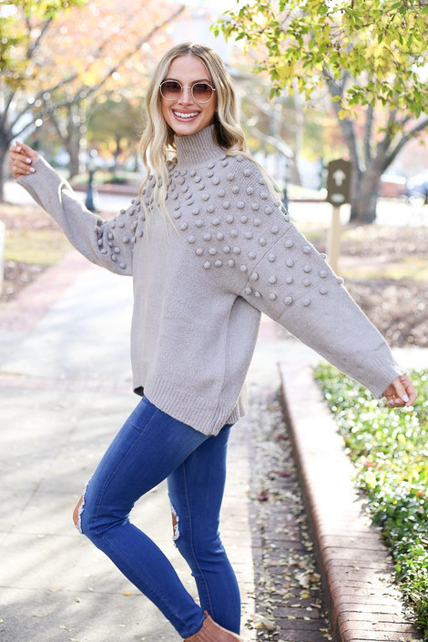Model wearing the Mock Neck Pom Pom Sweater from Dress Up Boutique in Grey - Side View