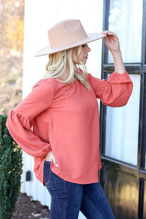 Rust - Model wearing a balloon sleeve blouse with wide brim hat