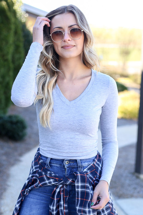 Model wearing the Heather Grey Long Sleeve Basic Crop Top with flannel and medium wash jeans Front View