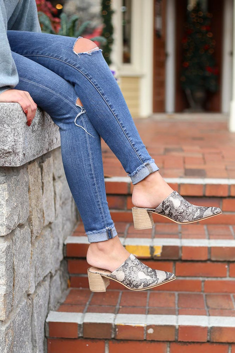 Snake - Side view of snakeskin block heel mules paired with jeans