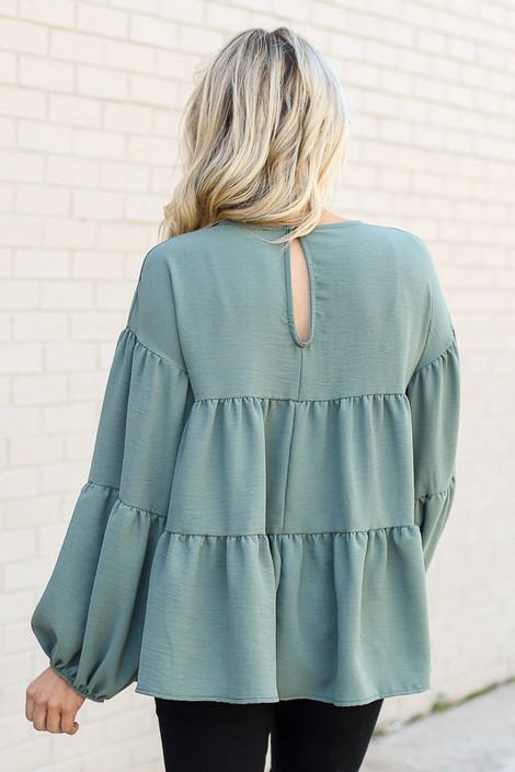 Model wearing the Tiered Babydoll Blouse in Olive from Dress Up Back View
