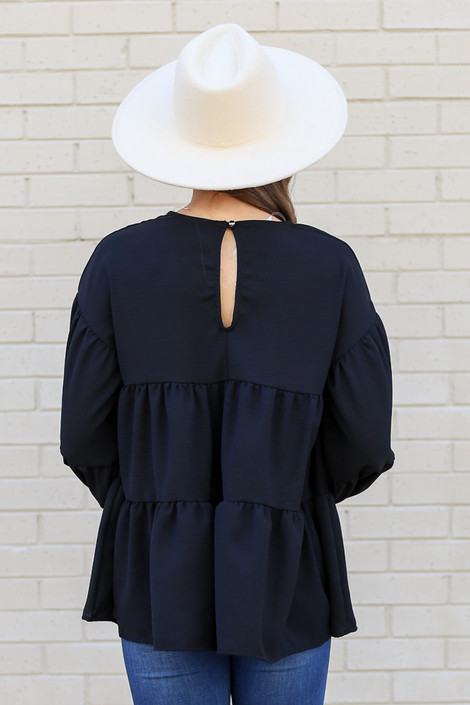 Model wearing the Tiered Babydoll Blouse in Black from Dress Up Back View