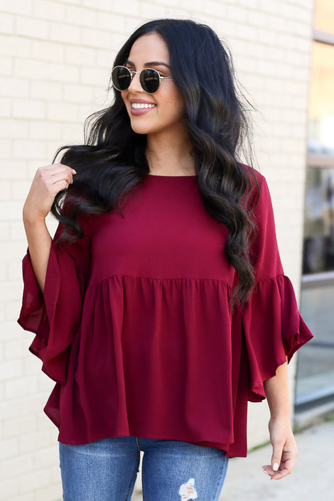 Model wearing the Ruffle Sleeve Babydoll Blouse from Dress Up in burgundy with medium wash jeans Front View