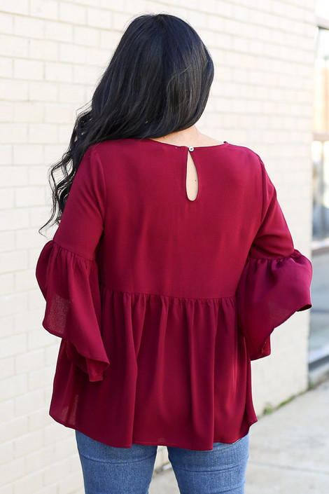 Model wearing the Ruffle Sleeve Babydoll Blouse from Dress Up in burgundy with medium wash jeans Back View