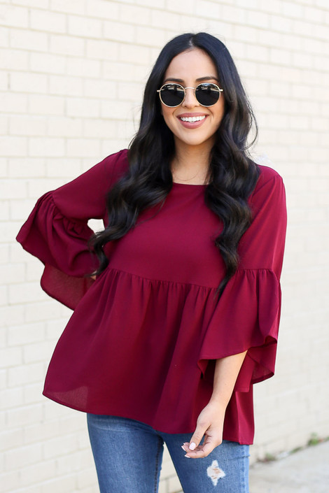 Model of Dress Up wearing the Ruffle Sleeve Babydoll Blouse in burgundy with distressed jeans Front View