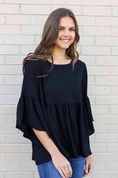 Model wearing the Ruffle Sleeve Babydoll Blouse from Dress Up with medium wash jeans Front View