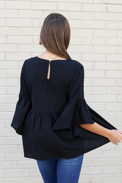 Model wearing the Ruffle Sleeve Babydoll Blouse from Dress Up with medium wash jeans Back View