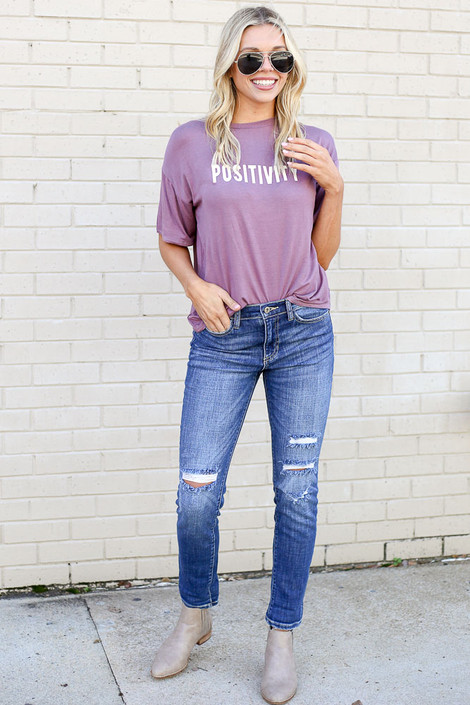 Model from Dress Up wearing the Medium Wash High Rise Distressed Skinny Jeans with Purple Graphic Tee