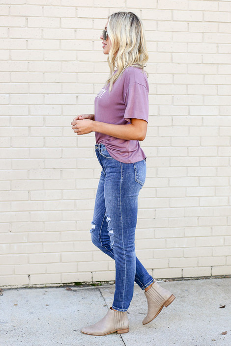 Model from Dress Up wearing the Medium Wash High Rise Distressed Skinny Jeans with Purple Graphic Tee - Side View
