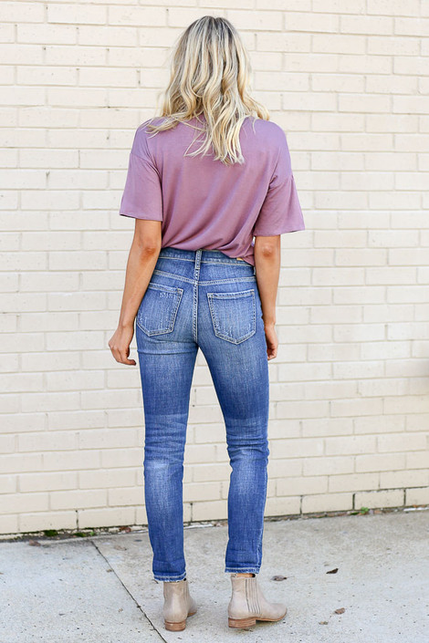Model from Dress Up wearing the Medium Wash High Rise Distressed Skinny Jeans with Purple Graphic Tee - Back View