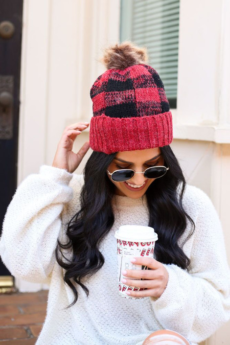 Model wearing the Red Buffalo Plaid Pom Pom Beanie from Dress Up with white sweater