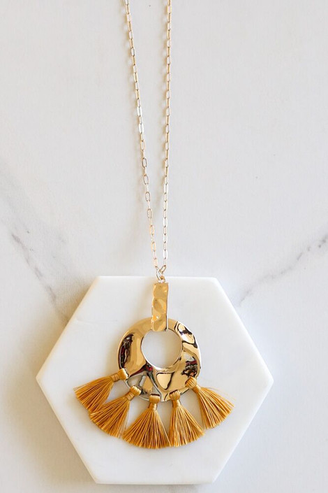 Mustard - Hammered Gold and Tassel Statement Necklace flat lay on marble