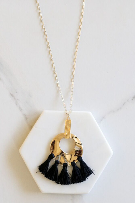Black - Hammered Gold and Tassel Statement Necklace flat lay on marble background