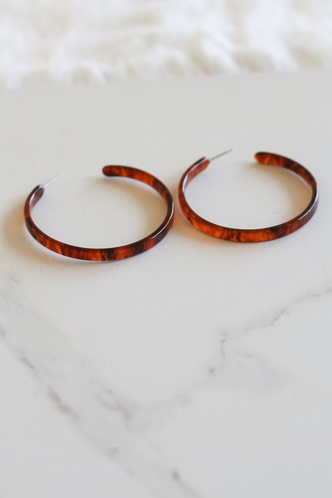 Red - Skinny Tortoise Hoops from Dress Up Boutique flat lay on marble