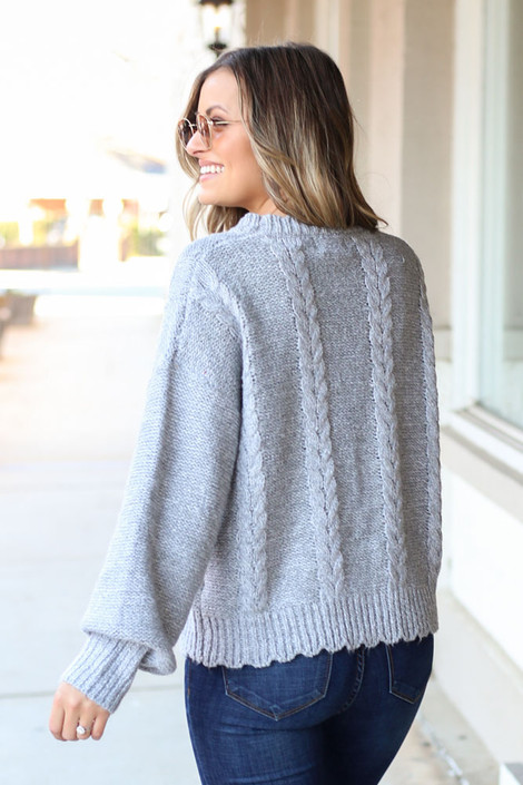 Model wearing the Cable Knit Pom Pom Sweater with jeans Back View
