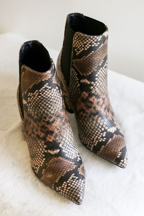 Brown Snakeskin Chelsea Booties from Dress Up flat lay on faux fur background