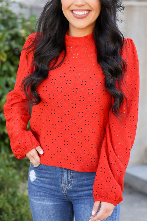 Model wearing the Mock Neck Eyelet Blouse in Rust with High Rise Jeans Close Up View