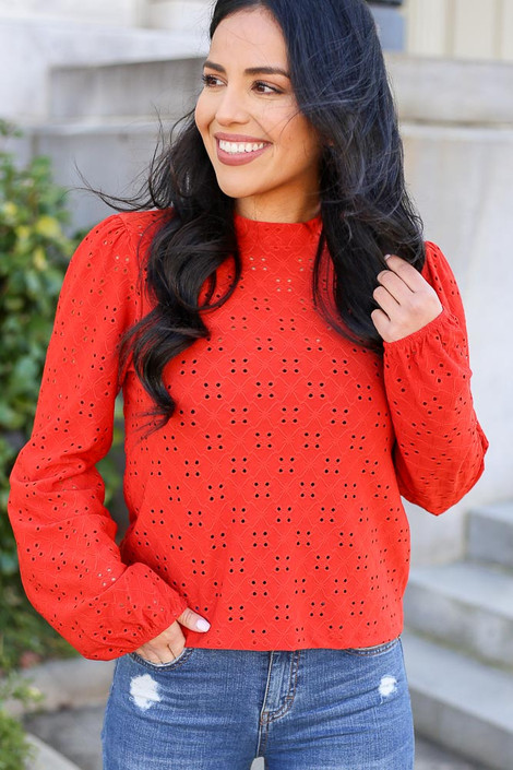 Model wearing the Mock Neck Eyelet Blouse in Rust with High Rise Jeans Front View