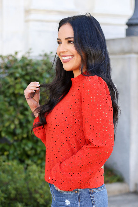 Model wearing the Mock Neck Eyelet Blouse in Rust with High Rise Jeans Side View