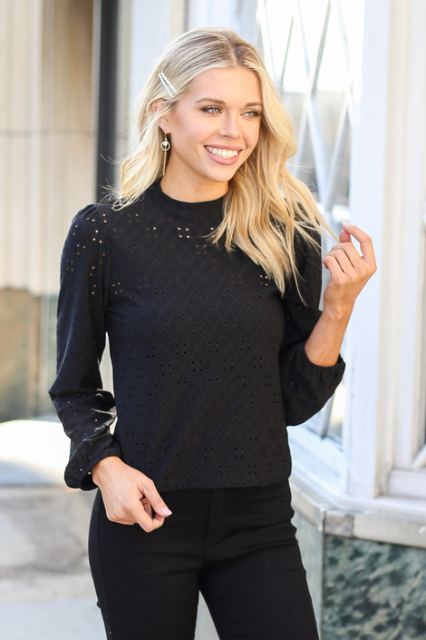 Model wearing the Mock Neck Eyelet Blouse in Black with Black Skinny Jeans Front View