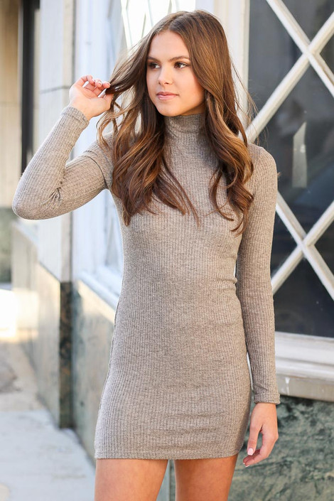 Model wearing the Ribbed Bodycon Dress in Brown with hand in hair with window in background Front View