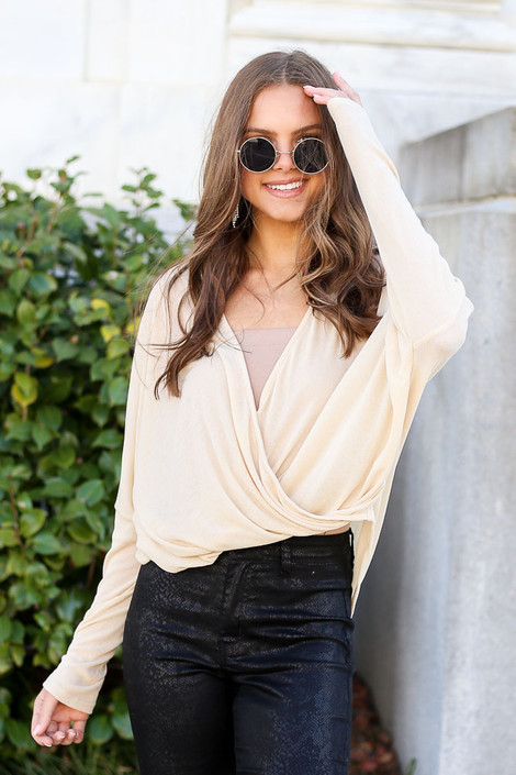 Model from Dress Up wearing the Drop Sleeve Surplice Top in Taupe with snakeskin faux leather jeans and sunglasses