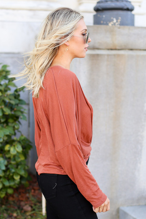 Model from Dress Up wearing the Drop Sleeve Surplice Top in Rust with Black Skinny Jeans Side View