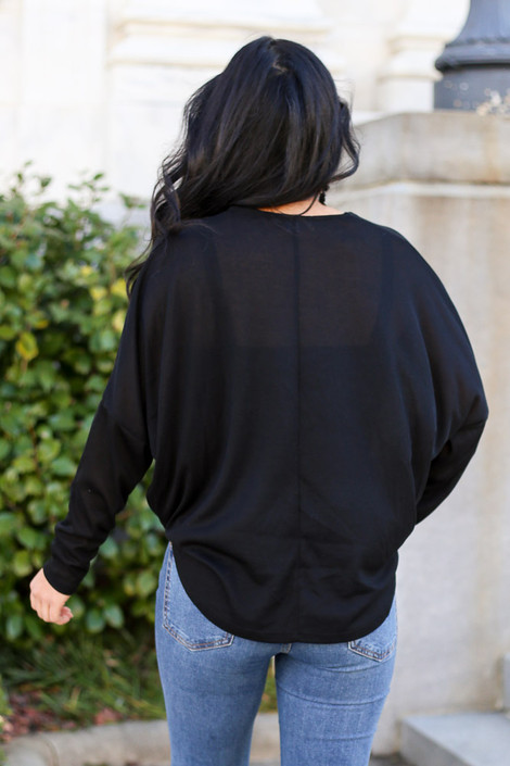 Model from Dress Up wearing the Drop Sleeve Surplice Top with distressed jeans Back View