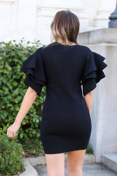 Model from Dress Up wearing the Ruffle Sleeve Sweater Dress in Black Back View