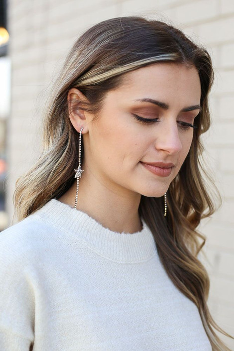 Model wearing the Gold Rhinestone Star Drop Earrings from Dress Up