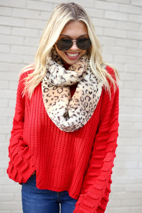 Model wearing the Alicia Leopard Faux Fur Infinity Scarf from Dress Up with red sweater and jeans front view