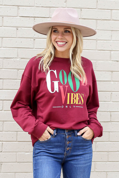 Model wearing the Good Vibes Only Vintage Graphic Pullover with skinny jeans