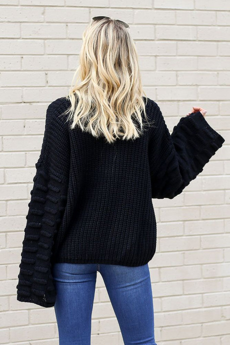 Model wearing the Textured Knit Wide Sleeve Sweater in Black from Dress Up Back View