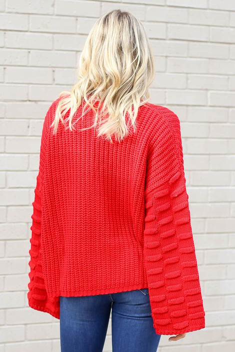 Model wearing the Textured Knit Wide Sleeve Sweater in Red from Dress Up Back View