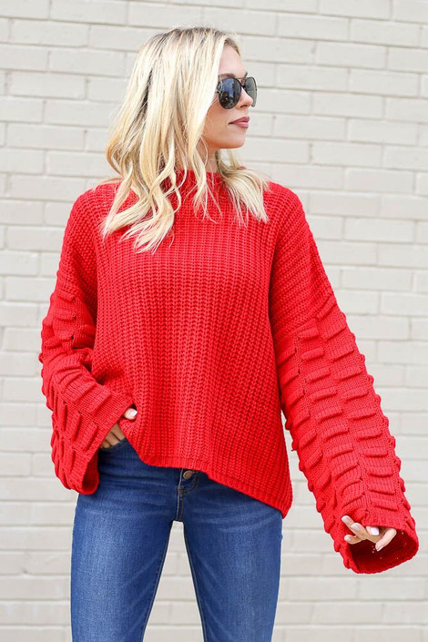 Model wearing the Textured Knit Wide Sleeve Sweater in Red with high rise jeans from Dress Up Front View