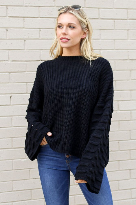 Model wearing the Textured Knit Wide Sleeve Sweater in Black with high rise jeans from Dress Up Front View