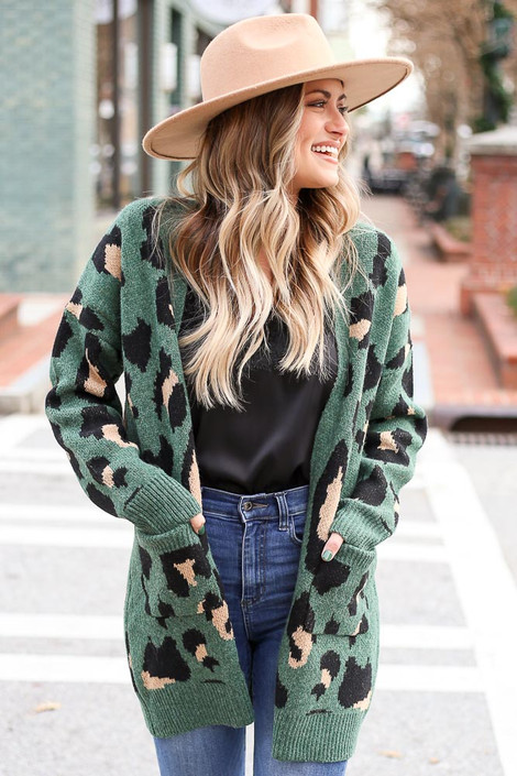 Model wearing the Leopard Longline Cardigan Sweater in Green with wide brim hat and medium wash jeans from Dress Up Front View