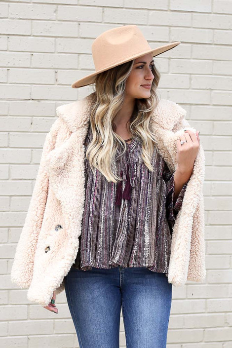 Model wearing the Gauze Bell Sleeve Babydoll Top with a sherpa jacket