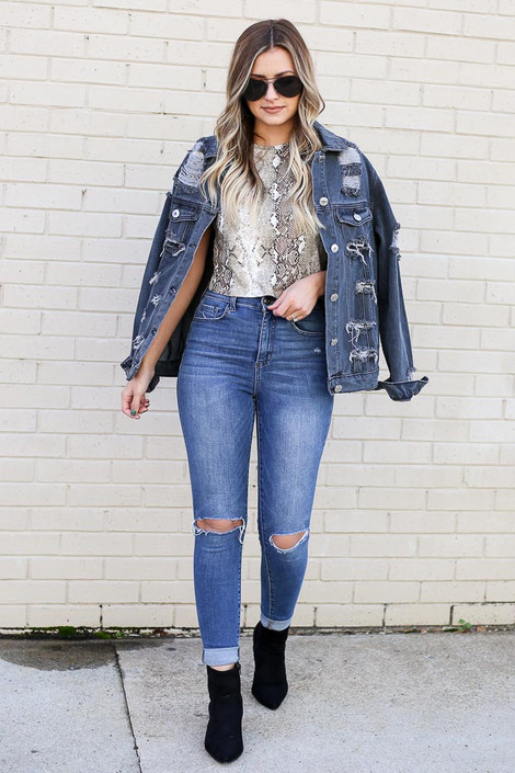 Model from Dress Up wearing Snakeskin Crop Top styled with Distressed Jeans, Ankle Booties, and Distressed Denim Jacket Back View