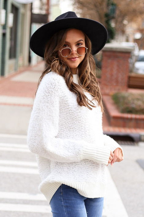 Model wearing the White Oversized Popcorn Eyelash Knit Sweater with medium wash jeans from Dress Up Side View