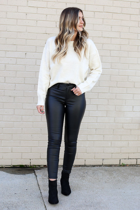 Model wearing the Mid Rise Faux Leather Skinny Jeans from Dress Up with knit sweater with ankle booties